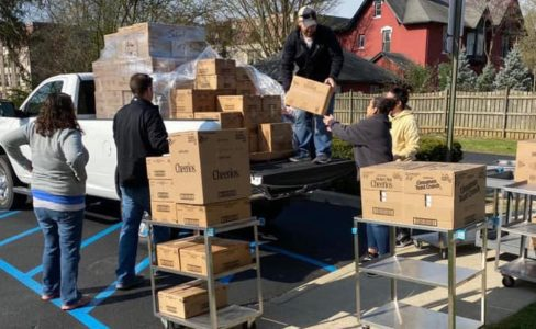 Volunteers and CIS staff members help unload a pickup truck filled with boxes of donated items.