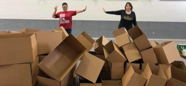 Two CIS staff members stand behind a pile of empty boxes used to distribute needed supplies to area families.